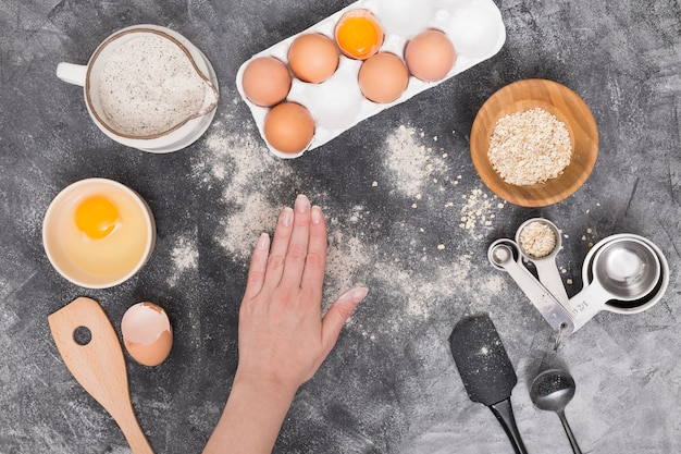 A person's hand with bread ingredients on black textured background Free Photo