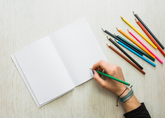 Person's hand writing on blank white book using color pencil Free Photo