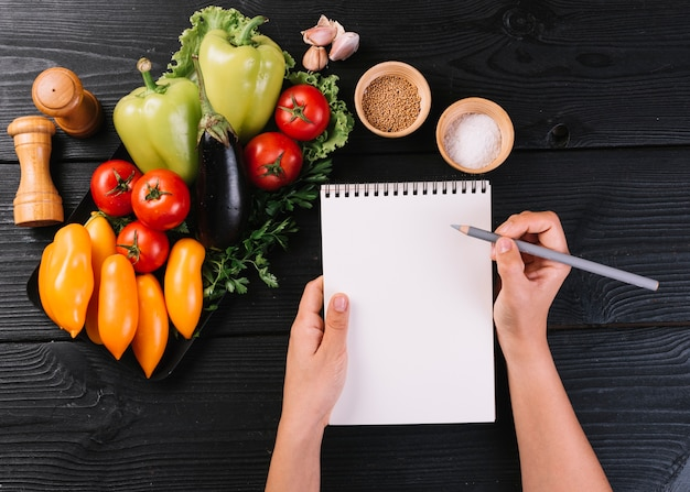 Person's hand writing on spiral notepad near vegetables and spices on black wooden surface Free Photo