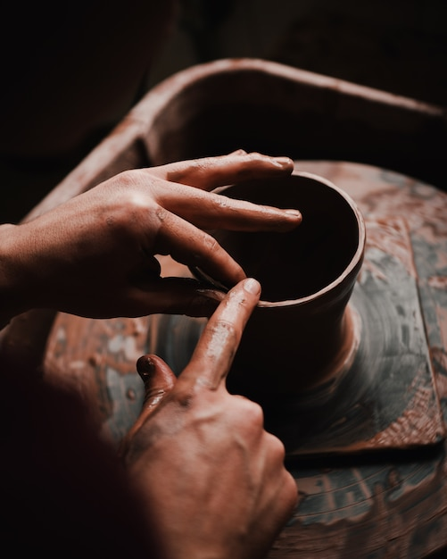 Person's hands and fingers crafting a clay pot Free Photo
