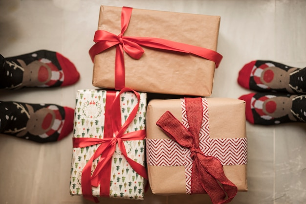 Person's legs in christmas socks near present boxes Free Photo
