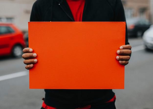 Лицо, показывающее пустую доску для поддержки движения Premium Фотографии