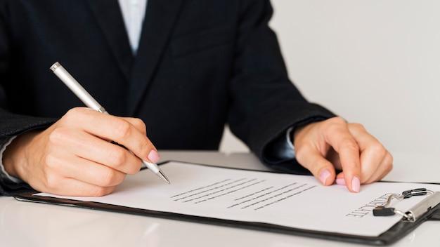 Persona che firma una vista frontale del certificato Foto Gratuite