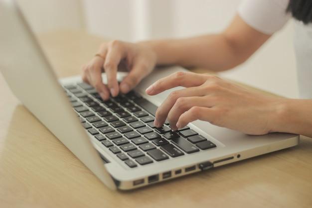 책상 앞에 앉아 노트북의 키보드에 입력하는 사람 무료 사진