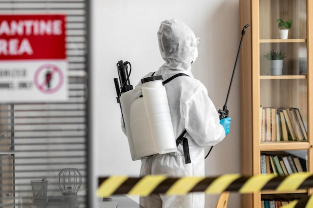 Person in special equipment disinfecting a restricted area Free Photo