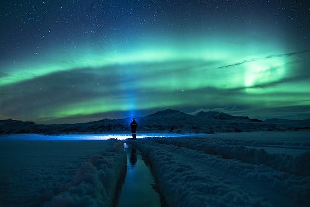 緑の空の下で雪に覆われた地面に立っている人 無料写真