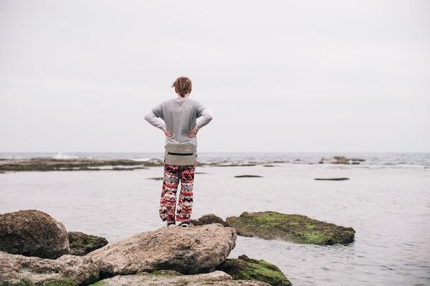 水域の苔むした岩の上に立っている人 無料写真