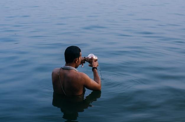 Persona in piedi in acqua mentre svuota la ciotola di rame in india Foto Gratuite