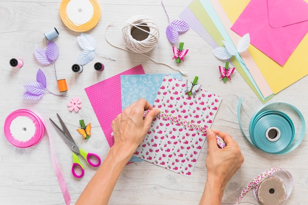 A person sticking ribbon over the scrapbook card on table Free Photo
