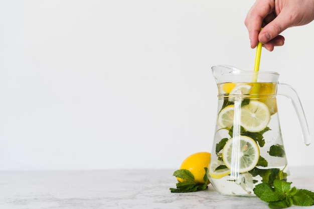 Person stirring lemon drink with mint in jug Free Photo