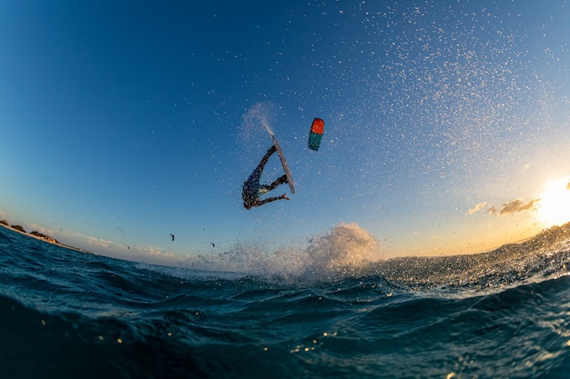 Person surfing and flying a parachute at the same time in kitesurfing. bonaire, caribbean Free Photo