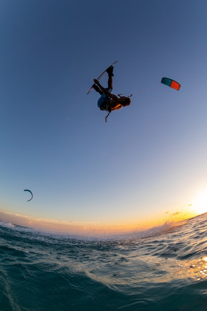 Person surfing and flying a parachute at the same time in kitesurfing Free Photo