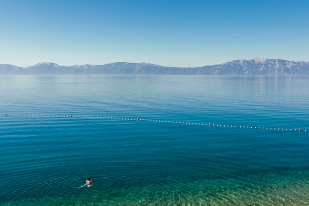 A person swimming in the blue idyllic lake Free Photo