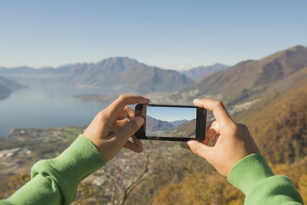 스위스의 마조 레 알파인 호수와 산의 사진을 찍는 사람 무료 사진