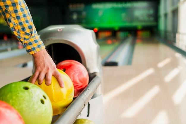 Persona che prende una palla da bowling Foto Gratuite