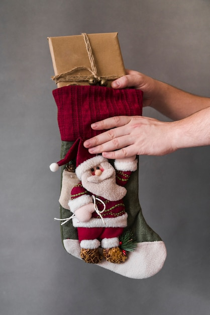 Person taking gift box from christmas sock Free Photo