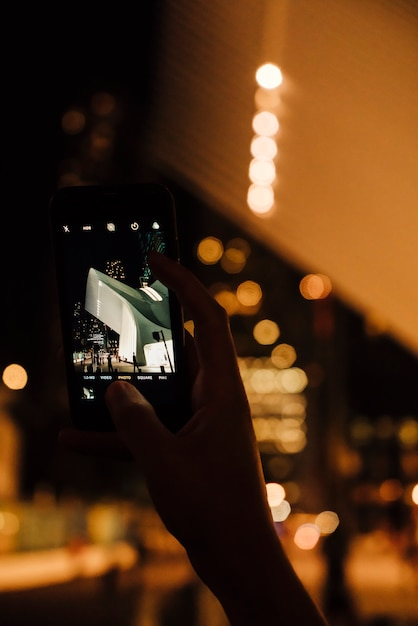 Person taking picture of modern architecture in night city on mobile phone Free Photo
