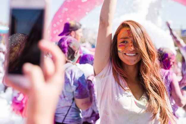 A person taking selfie of her smiling female friend on mobile phone during holi Free Photo