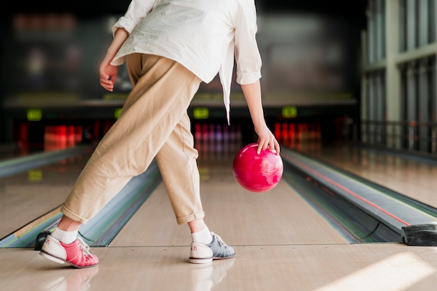 Persona che lancia una palla da bowling rossa Foto Gratuite