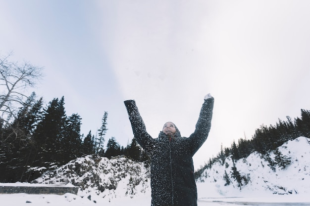 Person throwing snow on forest background Free Photo
