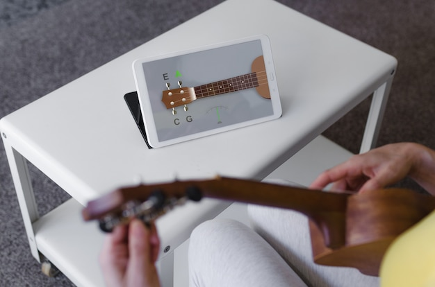Person tuning her ukulele with an app on her tablet Premium Photo
