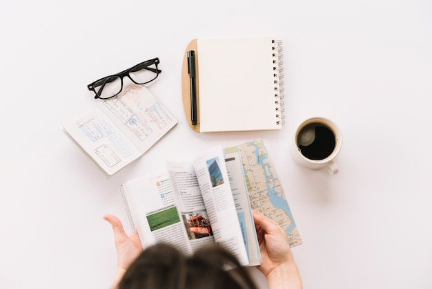 A person turning the pages of tourist guide book with passport; eyeglasses; spiral notepad and coffee cup on white backdrop Free Photo
