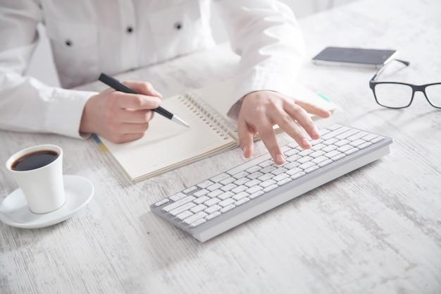 キーボードで入力してメモ帳に書き込む人。 Premium写真