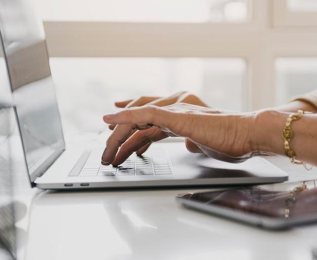 Person typing on laptop keyboard Free Photo