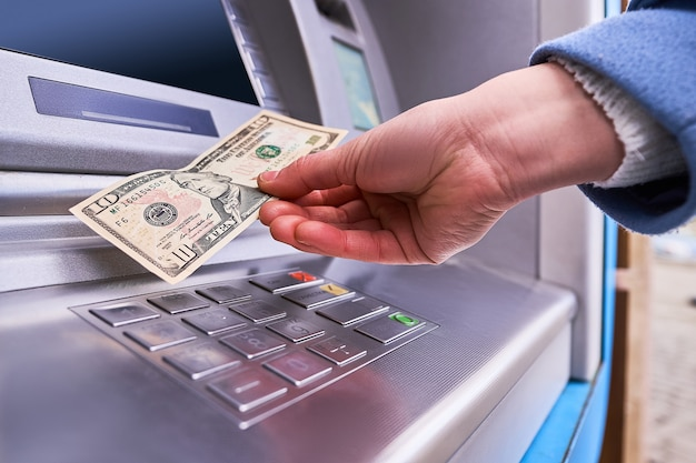 Person using automatic atm banking to withdraw money Premium Photo