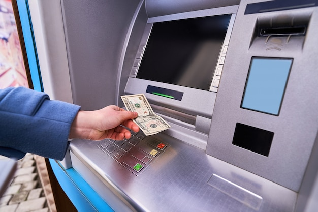 Person using street atm bank to withdraw cash Premium Photo