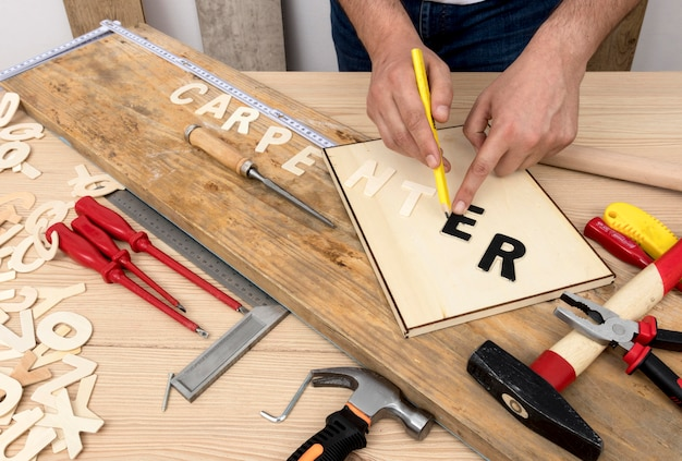 Person using tools to create carpentry word Free Photo