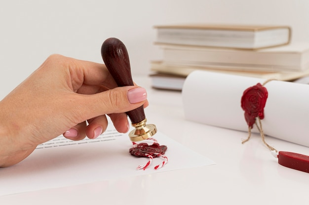Person using wax seal on certificate front view Premium Photo