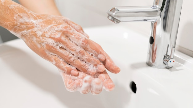 Person washing hands with soap Free Photo