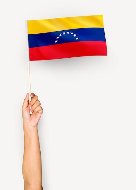 Человек, размахивающий флагом боливарианской республики венесуэла Бесплатные Фотографии