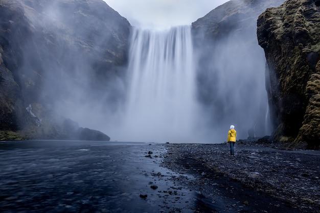 Человек в желтой куртке стоит у завораживающего водопада Бесплатные Фотографии