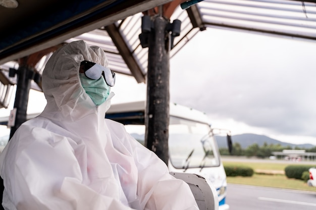 防護服を着た人、マスク付きのppe、バスに乗ってターミナルの外の飛行機の駐車場に入る Premium写真