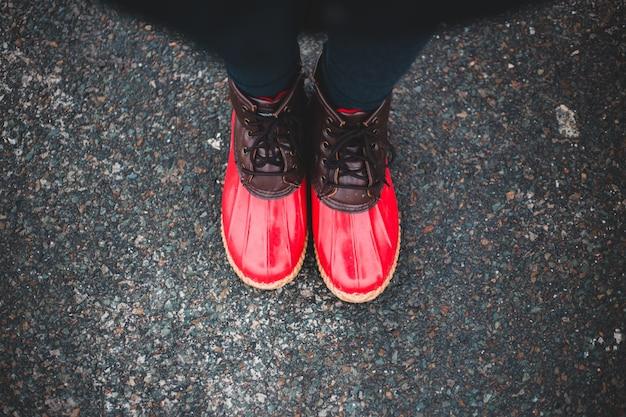 赤と黒の運動靴を履いている人 無料写真