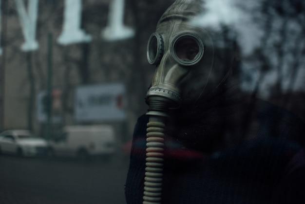Persona che indossa un respiratore in piedi dietro il vetro Foto Gratuite