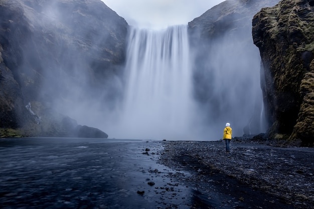 Person wearing a yellow jacket standing at the mesmerizing waterfall Free Photo