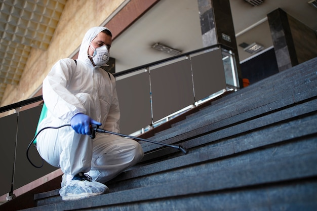 Persona in tuta di protezione chimica bianca che disinfetta corridoi pubblici e gradini per fermare la diffusione del virus corona altamente contagioso Foto Gratuite