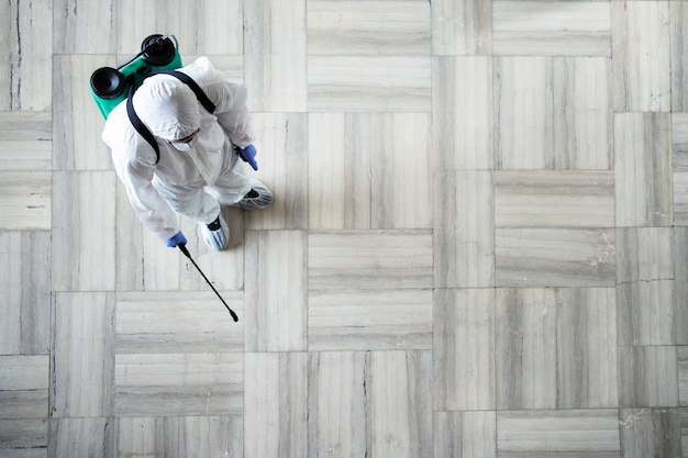 Person in white chemical protection suit doing disinfection of public areas to stop spraying highly contagious corona virus Free Photo