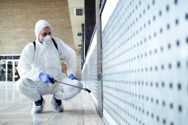 Persona in tuta di protezione chimica bianca che esegue la disinfezione delle aree pubbliche per fermare la diffusione del virus corona altamente contagioso Foto Gratuite