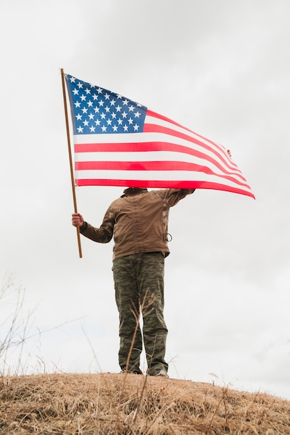 Person with american flag on hill Free Photo