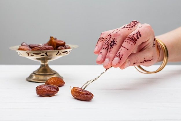 Person with mehndi holding date fruit with fork Free Photo