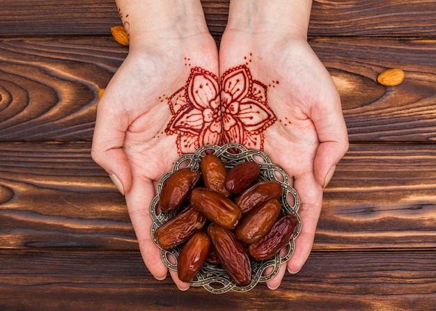 Person with mehndi holding plate with dates fruit Free Photo