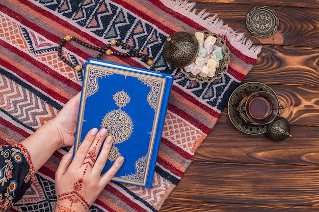 Person with mehndi holding quran near turkish delight Free Photo