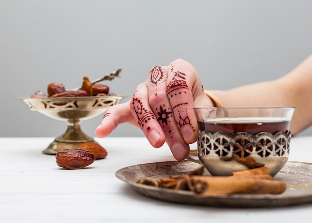 Person with mehndi holding tea cup on table Free Photo