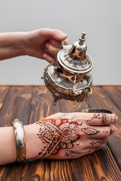 Person with mehndi pouring tea into cup Free Photo