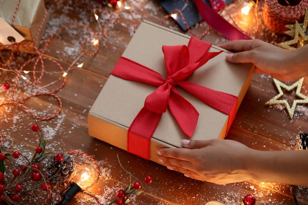 Person wrapping christmas present Free Photo