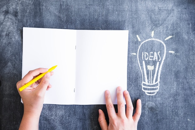 A person writing on paper with yellow crayon and drawn light bulb on chalkboard Free Photo